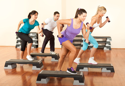 group of people exercising with dumbbells in the fitness club
